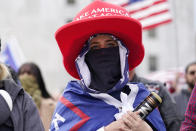 A protester holds a baseball bat while standing Saturday, Nov 7, 2020, in Salem, Ore., after Democrat Joe Biden defeated President Donald Trump to become 46th president of the United States. (AP Photo/Marcio Jose Sanchez)