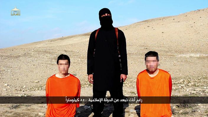 Screen grab taken on January 20, 2015 from a video reportedly released by the IS group through Al-Furqan Media allegedly shows Japanese hostages Kenji Goto (L) and Haruna Yukawa (R) with a militant as he addresses the camera in English (AFP Photo/)