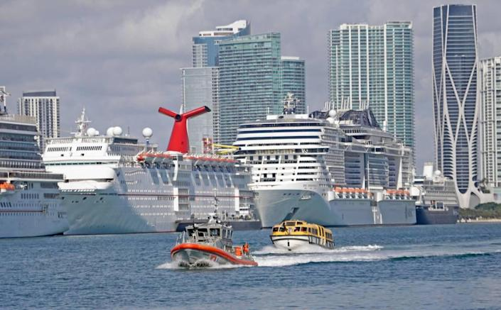A lifeboat from the Costa Magica cruise ship is escorted by U.S. Coast Guard vessel after it dropped off crew members at PortMiami on Monday, March 30, 2020. Crew members left on a charter flight to Manila, Philippines that evening.