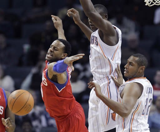 Philadelphia 76ers' Andre Iguodala, left, loses the ball as he is guarded by Charlotte Bobcats' Boris Diaw, right, and Bismack Biyombo during the first half of an NBA basketball game in Charlotte, N.C., Monday, Feb. 13, 2012. (AP Photo/Chuck Burton)
