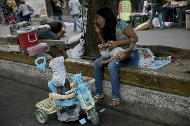 A woman with two children stops prior to crossing the Simon Bolivar International bridge into Colombia, in San Antonio del Tachira, Venezuela, Thursday, Feb. 21, 2019. Opposition leaders led by self-proclaimed interim president Juan Guaido are vowing to bring in U.S. supplies of emergency food and medicine to dramatize the country's hardships under President Nicolas Maduro, who has said the country doesn't need such help. (AP Photo/Rodrigo Abd)