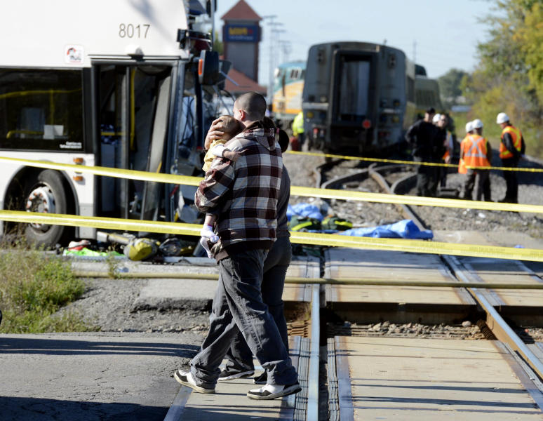 A man carries a child following a Via Rail train and city bus collision in Ottawa's west end Wednesday, Sept. 18, 2013. Multiple people were killed when a passenger train collided with a city bus at a crossing at the peak of morning rush hour, police said Wednesday. Rescue crews swarmed over the wreckage. The injured from the bus who would walk were taken to a second bus nearby to be treated by paramedics. The train tracks in the area cross both a major city street and a transit line reserved for buses only. (AP Photo/The Canadian Press, Adrian Wyld)