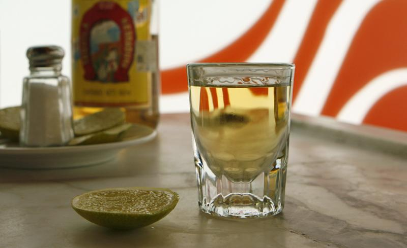 FILE - In this Aug. 28, 2006 file photo, a shot of aged Tequila Herradura with a lemon and salt fixings sit on a bar in front of bottles of white and aged Tequila Herradura in Mexico City, Mexico. Agave farmers see the expansion of China's middle class as their ticket to more sales. (AP Photo/Dario Lopez-Mills, File)