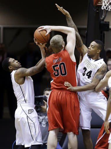 Ball State center Zach Fields (50) has his shot blocked by Purdue forward Jacob Lawson, right, as he is fouled from behind by Purdue guard Terone Johnson in the first half of an NCAA college basketball game in West Lafayette, Ind., Tuesday, Dec. 18, 2012. (AP Photo/Michael Conroy)