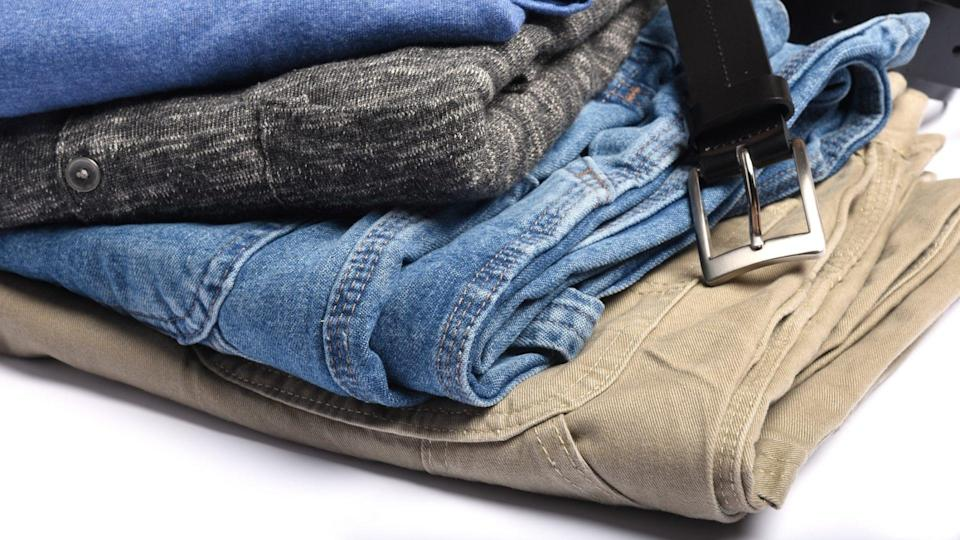 Folded jeans, shirts and sweaters with a belt.