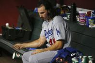 Los Angeles Dodgers starting pitcher Tony Gonsolin flips a cup to the ground as he sits in the dugout after being taken out of the baseball game right after giving up a two-run home run to Arizona Diamondbacks' Eduardo Escobar during the sixth inning of a baseball game Friday, Aug. 30, 2019, in Phoenix. (AP Photo/Ross D. Franklin)