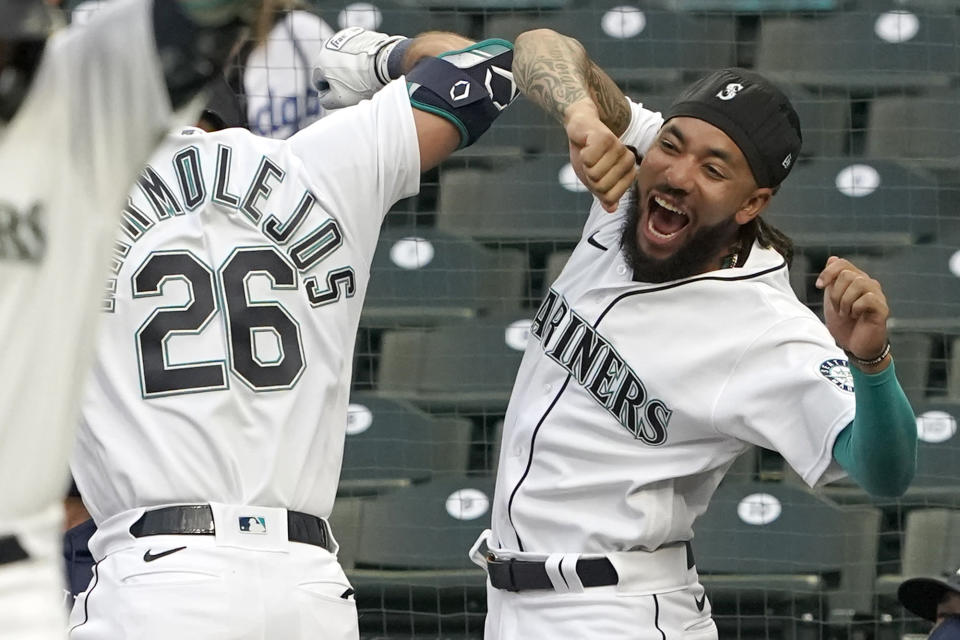 Seattle Mariners' Jose Marmolejos (26) is greeted by J.P. Crawford, right, at the dugout after hitting a two-run home run against the Los Angeles Dodgers during the first inning of a baseball game, Monday, April 19, 2021, in Seattle. (AP Photo/Ted S. Warren)