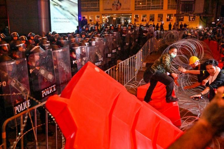 Pro-democracy protesters pushed barricades past barbed wire as riot police stood guard
