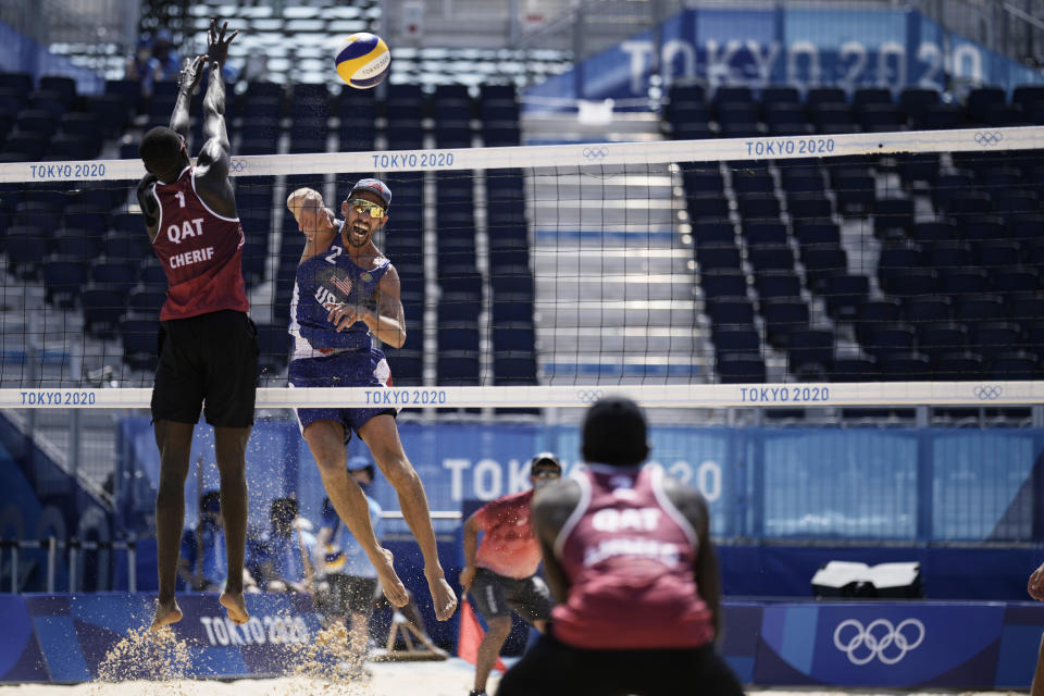Nicholas Lucena, center, of the United States, takes a shot as Cherif Younousse, left, of Qatar, and teammate Ahmed Tijan defend during a men's beach volleyball match at the 2020 Summer Olympics, Sunday, Aug. 1, 2021, in Tokyo, Japan. (AP Photo/Felipe Dana)