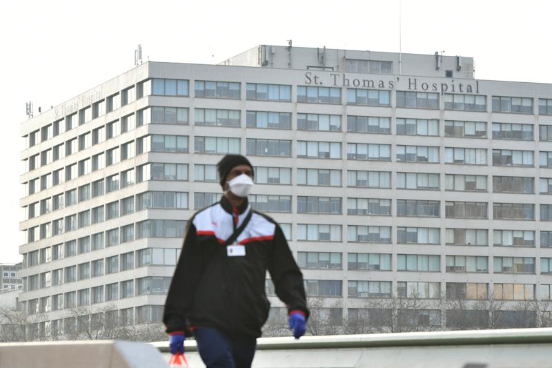 A man wearing a face mask walks near St Thomas' Hospital in Central London, where Prime Minister Boris Johnson remains in intensive care as his coronavirus symptoms persist. (Photo by Dominic Lipinski/PA Images via Getty Images)