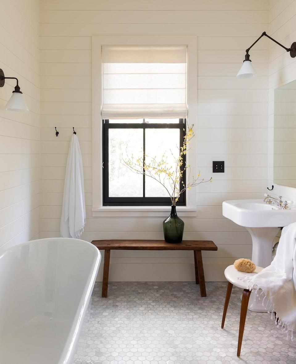 """<p>""""The <a href=""""https://www.marthastewart.com/7975822/how-convert-bathtub-to-shower"""" rel=""""nofollow noopener"""" target=""""_blank"""" data-ylk=""""slk:deep cast-iron tub"""" class=""""link rapid-noclick-resp"""">deep cast-iron tub</a> is in the guest bathroom, and looks out into the woods,"""" says Beers. """"The walls and ceilings in this room are all clad in paneling—we didn't want any drywall in the bathroom. It's great to sit in the tub and be able to have a conversation with someone in the adjacent bedroom when the door is open. It's also the perfect spot to bathe kids.""""</p>"""