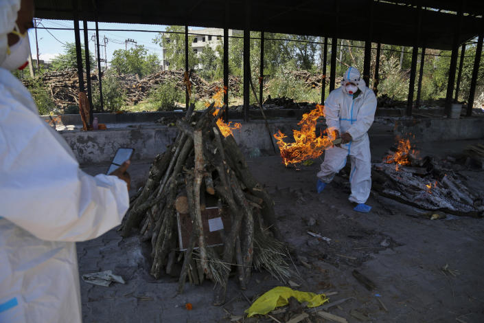 A family member lights the funeral pyre of a COVID-19 victim during cremation in Jammu, India, Monday, May 24, 2021. India crossed another grim milestone Monday of more than 300,000 people lost to the coronavirus as a devastating surge of infections appeared to be easing in big cities but was swamping the poorer countryside. (AP Photo/Channi Anand)