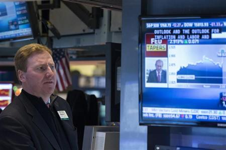 A trader listens to an announcement by the U.S. Federal Reserve on the floor of the New York Stock Exchange in New York