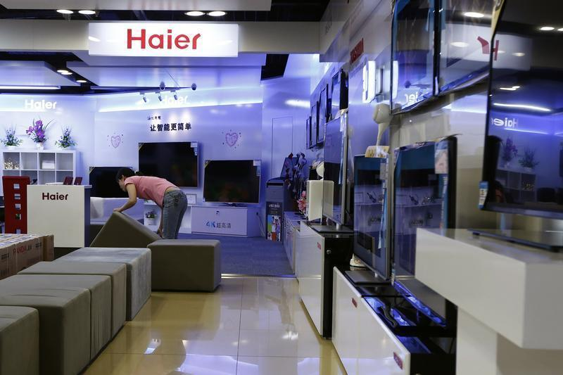 Employee arranges stools at a section displaying Haier television sets inside a Suning store in Shanghai