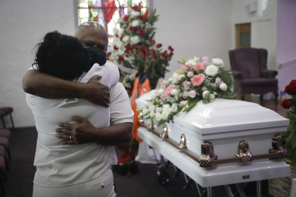 FILE - In this July 21, 2020, file photo, Darryl Hutchinson, facing camera, is hugged by a relative during a funeral service for Lydia Nunez, who was Hutchinson's cousin at the Metropolitan Baptist Church in Los Angeles. Nunez died from COVID-19. Southern California funeral homes are turning away bereaved families because they're running out of space for the bodies piling up during an unrelenting coronavirus surge. (AP Photo/Marcio Jose Sanchez, File)