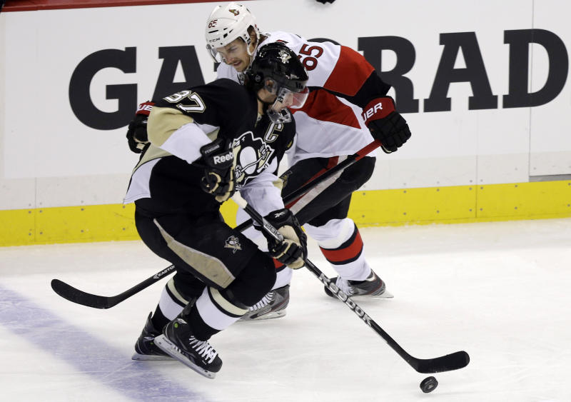 Pittsburgh Penguins' Sidney Crosby (87) gets past Ottawa Senators' Erik Karlsson (65) en route to a goal in the first period of Game 2 of an NHL hockey Stanley Cup second-round playoff series, in Pittsburgh on Friday, May 17, 2013. (AP Photo/Gene J. Puskar)