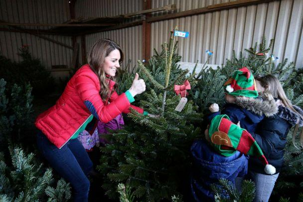 PHOTO: Britain's Catherine, Duchess of Cambridge moves a Christmas tree during a visit to Peterley Manor Farm where she took part in activities with families who are supported by the Family Action charity, in Buckinghamshire, England, Dec. 4, 2019. (Jonathan Brady/PA Wire via AP)
