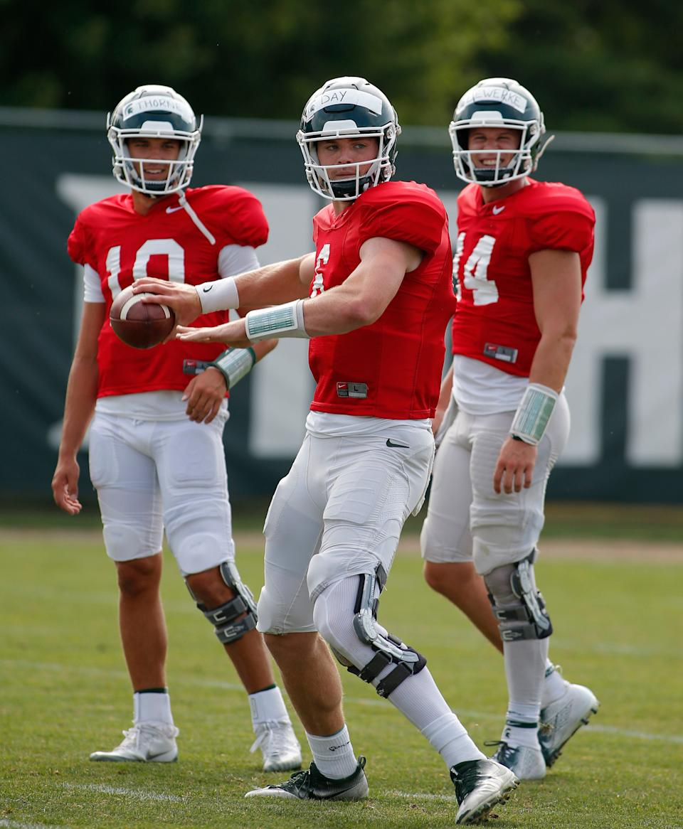 Michigan State quarterback Theo Day, center, throws a pass as Brian Lewerke, right, and Payton Thorne, left, watch during practice Aug. 12, 2019, in East Lansing.