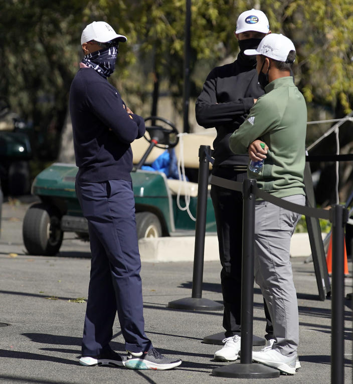From left, Tiger Woods, Dustin Johnson and Xander Schauffele talk after high winds suspended play during the third round of the Genesis Invitational golf tournament at Riviera Country Club, Saturday, Feb. 20, 2021, in the Pacific Palisades area of Los Angeles. (AP Photo/Ryan Kang)