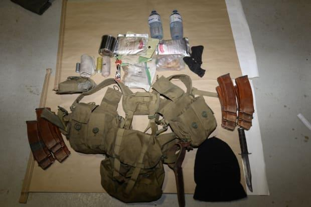An RCMP's Integrated National Security Enforcement Team have laid 34 charges against Kelvin Gregory Maure. It shared these photos of magazine pouches, a knife, and a balaclava. (RCMP - image credit)