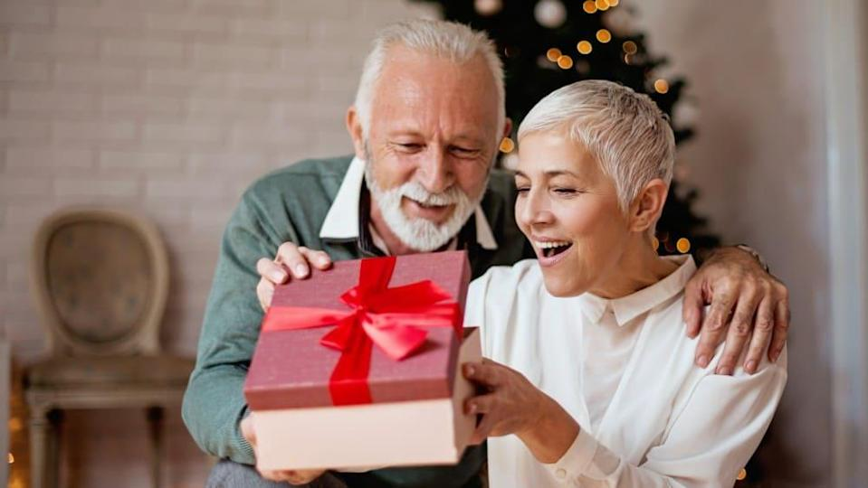 Elderly man giving a Christmas present to his wife