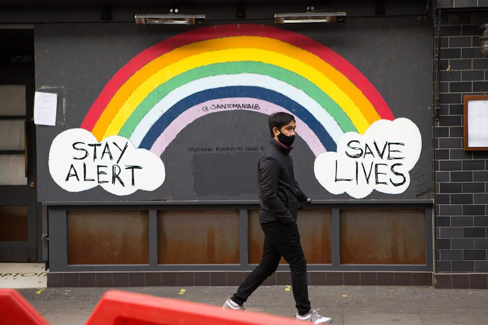 A man walks past a Stay Alert Save lives Rainbow sign in Soho during the second lockdown. London will be placed in tier 2 restrictions when England�s national lockdown comes to an end as all not essential shops will be closed until 2nd December. (Photo by Pietro Recchia / SOPA Images/Sipa USA)