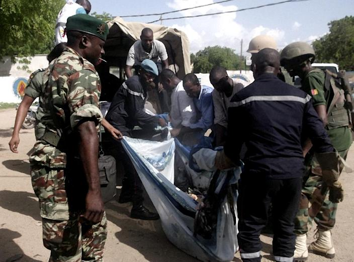 Security forces transport with a blanket the remains of some of the eleven victims of a double blast in the northern Cameroonian city of Maroua on July 22, 2015 (AFP Photo/)