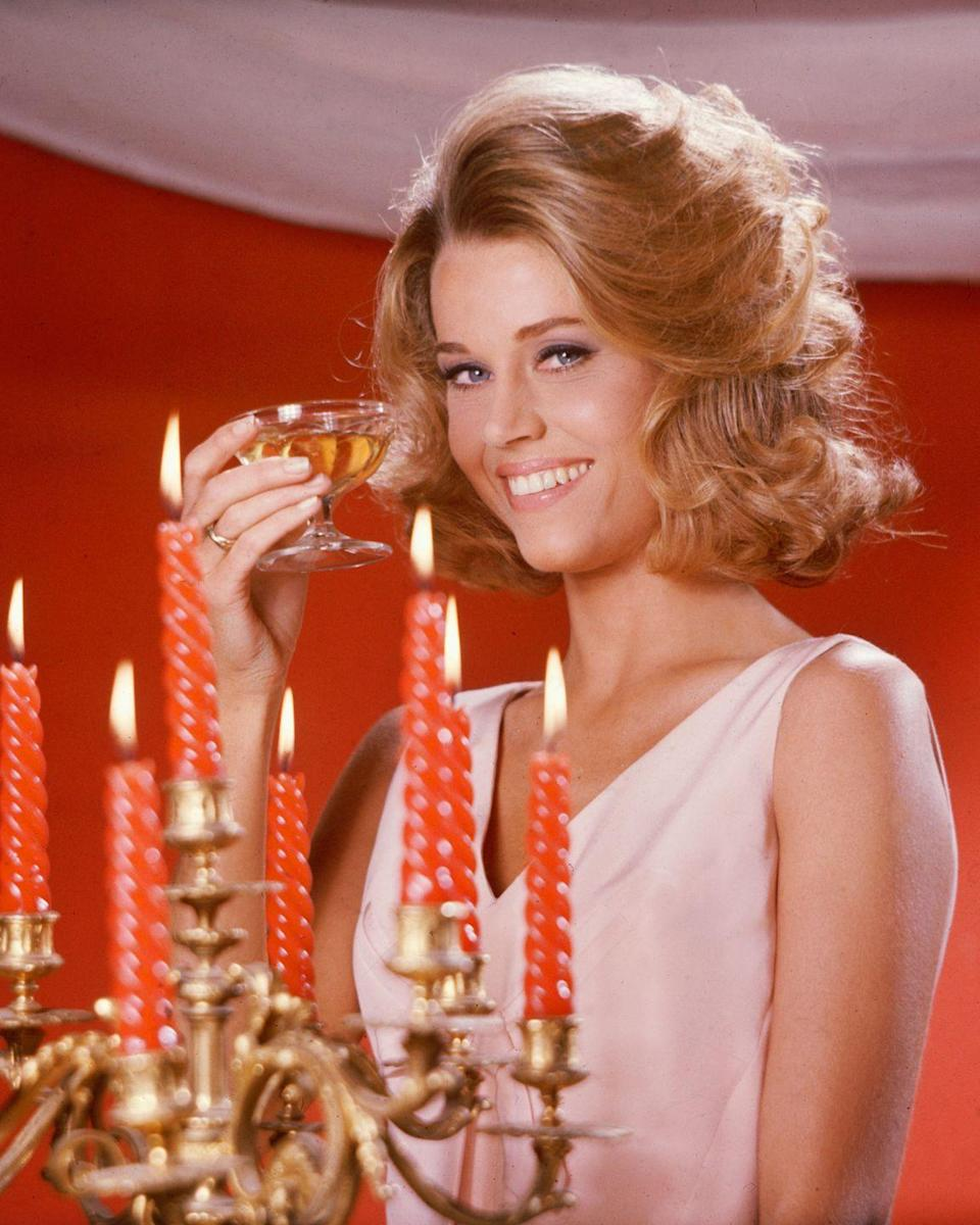 <p>Fonda poses with a coupe of champagne, wearing a pink sleeveless top, for a portrait. <br></p>