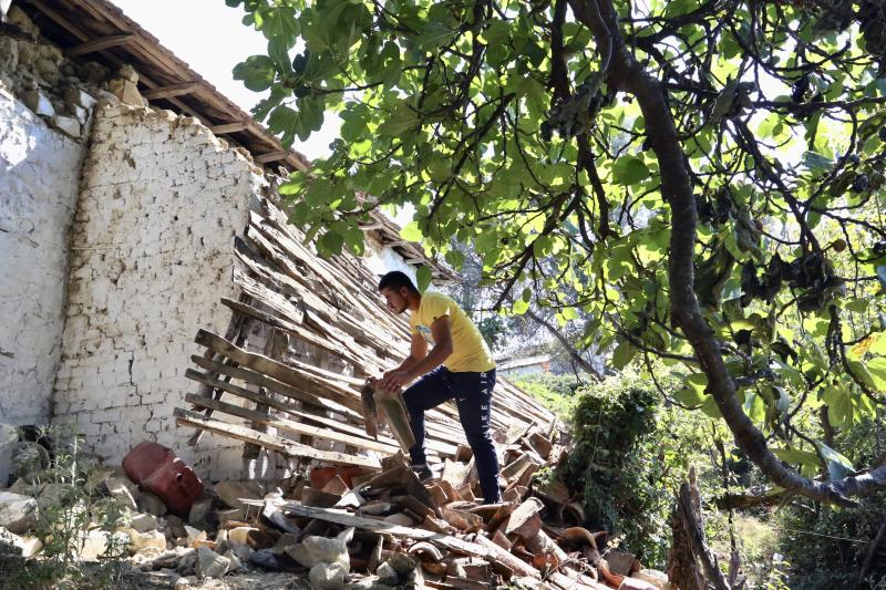 A man removes debris from a damaged house after an earthquake in Zhurje village, north of Tirana on Sunday, Sept. 22, 2019. Many residents in Albania's capital of Tirana and the port city of Durres have not gone back to their homes after a 5.8 magnitude earthquake injured 105 people and damaged hundreds of buildings. (AP Photo/Hektor Pustina)
