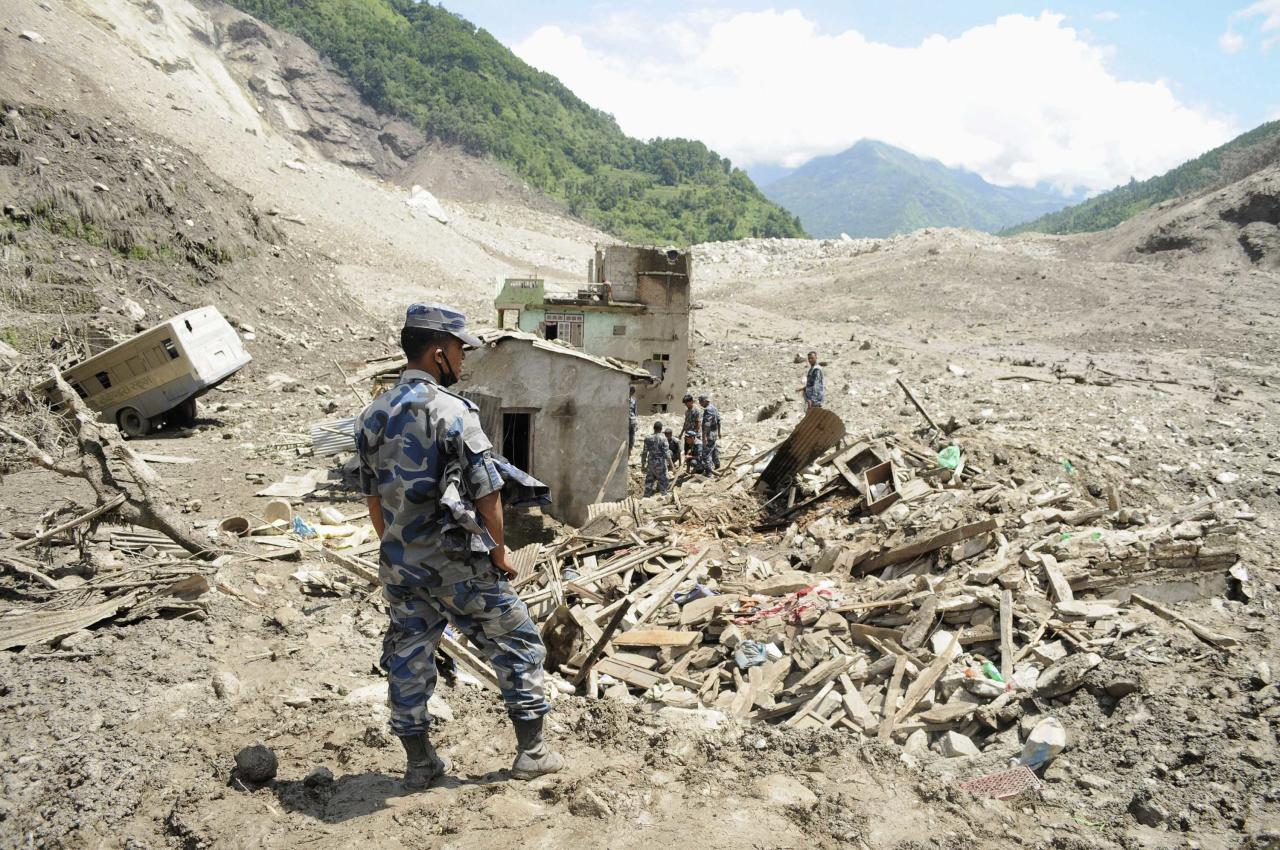 A rescue team from the Armed Police Force stands near damaged houses in the landslide area in Sindhupalchowk district August 2, 2014. A massive landslide triggered by heavy rains in northeast Nepal on Saturday has killed at least eight people, injured 40 and buried dozens of homes, officials said. The landslide created a mud dam blocking the Sunkoshi River near Jure in the Sindhupalchowk district, about 60 kms (37 miles) northeast of Kathmandu, heightening fears of downstream floods that could reach as far as Bihar in eastern India. REUTERS/Dipesh Shrestha (NEPAL - Tags: DISASTER ENVIRONMENT) NO SALES. NO ARCHIVES