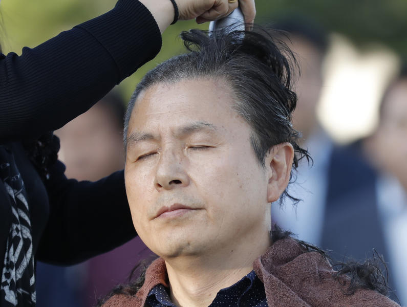 Hwang Kyo-ahn, the main opposition Liberty Korea Party chairman, has his head shaved in Seoul, South Korea, Monday, Sept. 16, 2019. The leader of South Korea's biggest opposition party has become the latest politician to shave their heads to protest President Moon Jae-in's appointment of a key political ally as justice minister despite allegations of academic fraud and financial crimes surrounding his family. (AP Photo/Lee Jin-man)