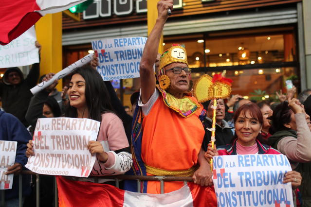 Demonstrators who had gathered to protest lawmakers pushing forward a vote to select an almost-full slate of new magistrates to the Constitutional Tribunal, celebrate after President Martin Vizcarra dissolved the legislature in Lima, Peru, Monday, Sept. 30, 2019. Lawmakers were pushing forward the vote despite Vizcarra's warning that the move threatens his fight against corruption and that he would dissolve the opposition-controlled legislature. (AP Photo/Martin Mejia)