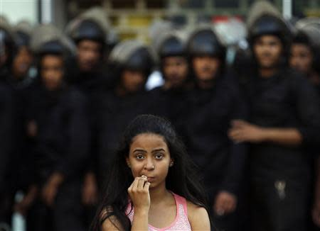 A female activist is pictured in front of riot police during a protest against a new law restricting demonstrations, in downtown Cairo