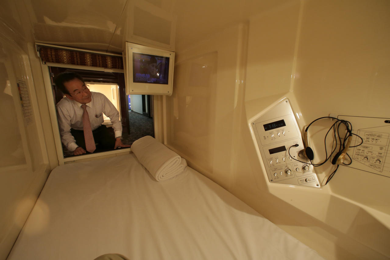 In this Monday, Oct. 29, 2012 photo, manager Akiyoshi Kaneko peers inside of a room at the Capsule & Sauna Century Shibuya in Tokyo. The capsule concept has been around for at least 30 years, starting out as lodging for businessmen working or partying late who missed the last train home and needed a cheap place to crash. But budget travelers and other folks curious about a unique lodging experience use them too. (AP Photo/Shizuo Kambayashi)