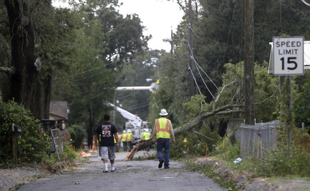 <p>Workers clear trees from power lines in Biloxi, Miss., in the aftermath of Hurricane Nate, Sunday, Oct. 8, 2017. (Photo: Gerald Herbert/AP) </p>