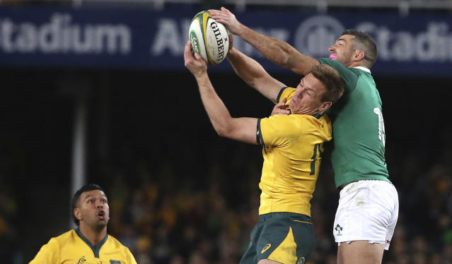 Australia's Dane Haylett-Petty, center, and Ireland's Rob Kearney, right, compete for a high ball during their rugby union test match in Sydney, Saturday, June 23, 2018. (AP Photo/Rick Rycroft)