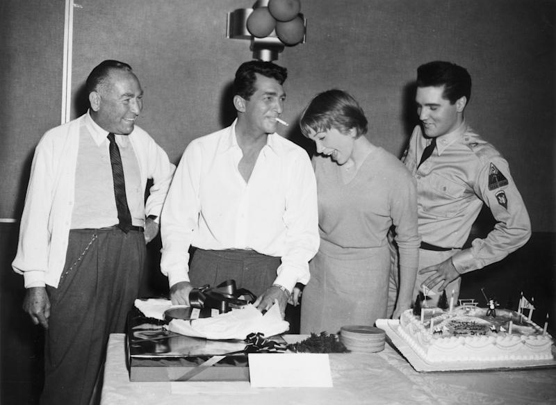 1961: American actor Dean Martin (1917 - 1995, second L), a cigarette dangling from his mouth, celebrates his birthday with producer Hal Wallis (L), actor Shirley MacLaine, and singer and actor Elvis Presley (1935 - 1977), while in production for director Joseph Anthony's film, 'All in a Night's Work'. Martin opens a gift next to his birthday cake, which reads 'Happy Birthday to Dean from Hal.' (Photo by Paramount Pictures/Getty Images)