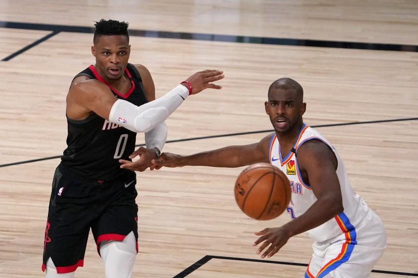 Houston Rockets' Russell Westbrook (0) makes a pass under pressure from Oklahoma City Thunder's Chris Paul, right, during the second half of an NBA first-round playoff basketball game in Lake Buena Vista, Fla., Wednesday, Sept. 2, 2020. (AP Photo/Mark J. Terrill)