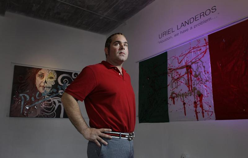 """In this Oct. 23, 2012 photo, James Perez, owner of Cueto James Art Gallery, poses between pieces titled """"Ego"""", left, and """"Legalize Drugs"""", right, that will be in the show titled """"Uriel Landeros: Houston We Have a Problem"""" in Houston. Uriel Landeros, is the man accused of vandalizing a Picasso painting at the Menil with spray paint in June. (AP Photo/Houston Chronicle, Melissa Phillip)"""