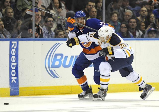 Buffalo Sabres' Henrik Tallinder (20) crashes into New York Islanders' Colin McDonald (13) to chase the puck in the second period of an NHL hockey game on Saturday, March 15, 2014, in Uniondale, N.Y. (AP Photo/Kathy Kmonicek)