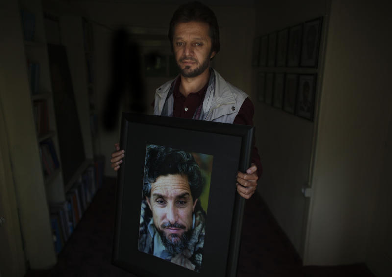 In this Wednesday, Oct. 3, 2012 photo, Fahim Dashti, executive of the National Journalists' Union, poses with a photograph of his wartime leader Ahmad Shah Massoud in Kabul Afghanistan. Dashti was with Massoud, the charismatic Tajik leader who commanded the Northern Alliance, when he was fatally wounded by two terrorists posing as journalists two days before the Sept. 11 attacks. (AP Photo/Dusan Vranic)
