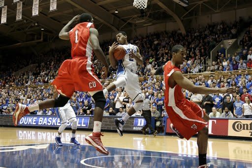 Duke's Quinn Cook drives into the lane against Cornell's Galal Cancer (1) and Johnathan Gray during the first half of an NCAA college basketball game in Durham, N.C., Wednesday, Dec. 19, 2012. (AP Photo/Gerry Broome)