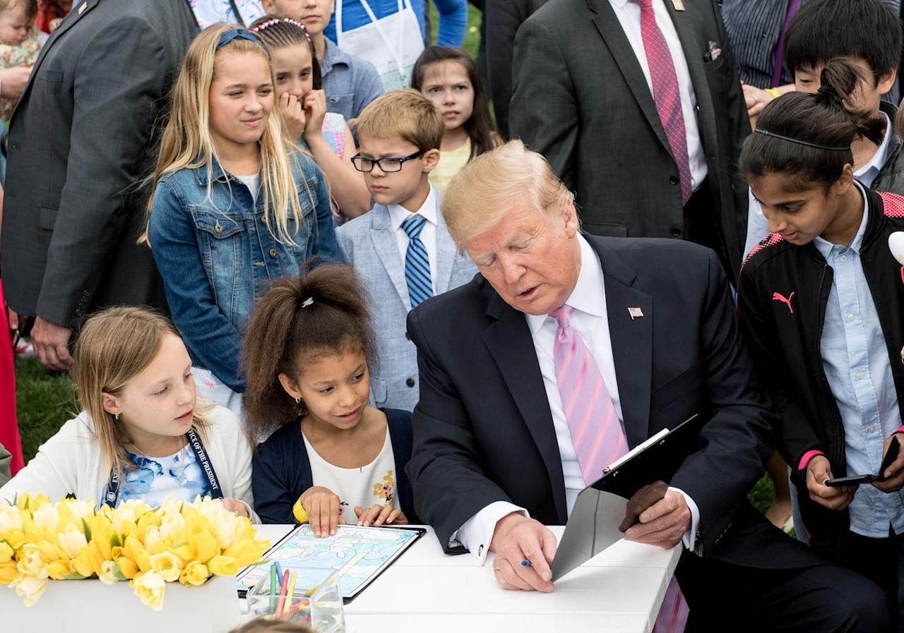 <p>Trump with children at a coloring table as he participates in the White House Easter Egg Roll.</p>
