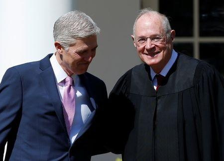 Judge Neil Gorsuch greets Justice Anthony Kennedy before being sworn in as an Associate Supreme Court Justice in the Rose Garden of the White House in Washington, U.S., April 10, 2017. REUTERS/Joshua Roberts