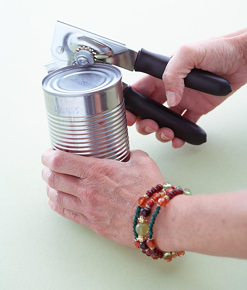 woman in bracelets opening can with can opener