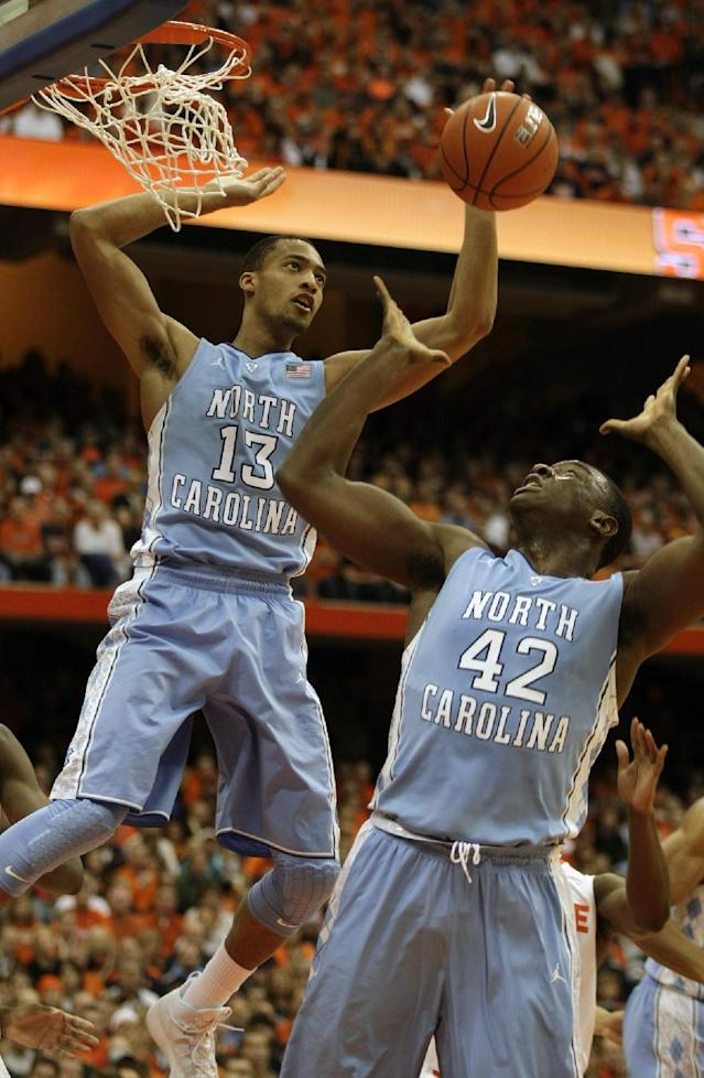 North Carolina's J.P. Tokoto, left, and Joel James, right, go for a rebound in the first half of an NCAA college basketball game against Syracuse in Syracuse, N.Y., Saturday, Jan. 11, 2014. (AP Photo/Nick Lisi)