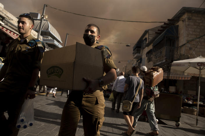An Israeli soldier carries a box of sandwiches as he walks with a fellow soldier through the Machane Yehuda market under a sky darkened by nearby wildfires, in Jerusalem, Sunday, Aug. 15, 2021.(AP Photo/Maya Alleruzzo)