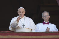Pope Francis, flanked by Mons. Guido Marini, the Vatican master of liturgical ceremonies, waves to faithful and pilgrims after he delivered the Urbi et Orbi (Latin for 'to the city and to the world' ) Christmas' day blessing from the main balcony of St. Peter's Basilica at the Vatican, Wednesday, Dec. 25, 2019. (AP Photo/Alessandra Tarantino)