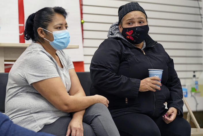 """Graciela Uraga, left, a cleaning lady, and Blanca Cedillos, a nanny, react as they watch Joe Biden's presidential inauguration from the Workers Justice Center, an immigrants rights center, Wednesday, Jan. 20, 2021, in the Sunset Park neighborhood of Brooklyn in New York. Cedillos admitted to being """"nervous"""" when the speech started, but after the speech, said she was disappointed Biden didn't mention immigration reform. (AP Photo/Kathy Willens)"""