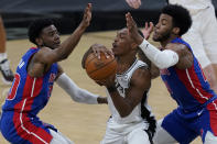 San Antonio Spurs guard Lonnie Walker IV, center, is pressured by Detroit Pistons guard Josh Jackson, left, and forward Saddiq Bey, right, during the second half of an NBA basketball game in San Antonio, Thursday, April 22, 2021. (AP Photo/Eric Gay)